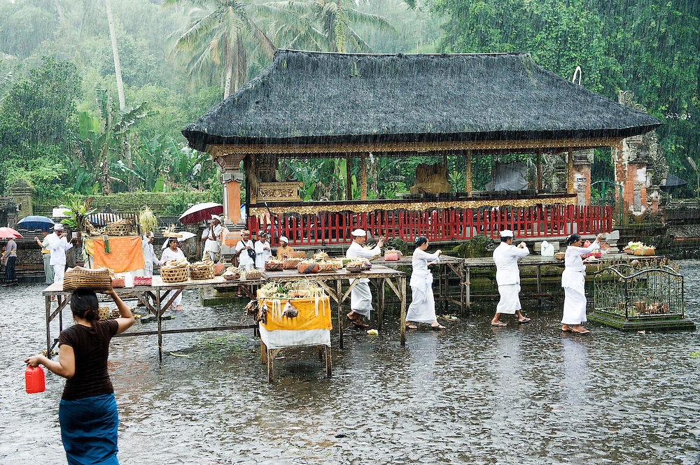 People walking under rain at Goa Gajah during a holy ceremony