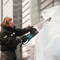 London, UK - 11 January 2012: Niall Magee works a block of ice with his chisel during the Ice sculpting festival 2013 in Canary Warf.