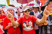 06 APRIL 2014 - BANGKOK, THAILAND: A woman dances with a tee shirt decorated with photos of Thaksin Shinawatra, the exiled former Prime Minister of Thailand and Yingluck Shinawatra, the current Prime Minister and Thaksin's sister. Red Shirts and supporters of the government of Yingluck Shinawatra, the Prime Minister of Thailand, gathered in a suburb of Bangkok this weekend to show support for the government. The Thai government is dealing with ongoing protests led by anti-government activists. Legal challenges filed by critics of the government could bring the government down as soon as the end of April. The Red Shirt rally this weekend was to show support for the government, which public opinion polls show still has the support of most of the electorate.   PHOTO BY JACK KURTZ
