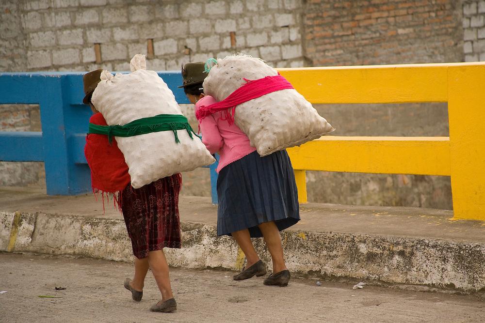 South America, Ecuador, Pujili, two women carry heavy loads on back