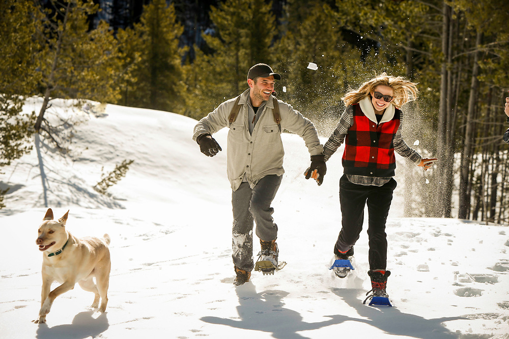 Sun Valley Idaho Winter for Woolrich National advertising of couple running in snowshoes with a dog and snow flying.