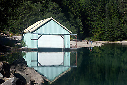 Boat house and reflection with two people walking dogs along the shore of Lake Diablo, North Cascades National Park, Washington, United States of America