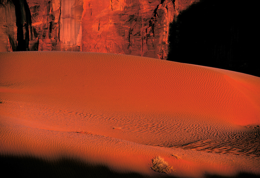 Sunset light turns a sand dune red in Monument Valley, Utah.
