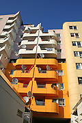 orange and white apartment block with many satellite dishes