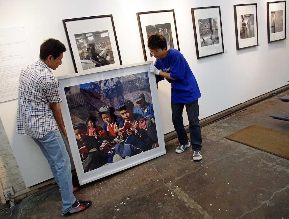 Woekers move a photo depecting a scene from the cultural revolution in Dazhanzi at Photogallery 798. China's art scene is becoming popular among foreign art collectors pushing prices higher.