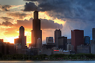 As summer storm clouds move in, the sun sets behind the Sears Tower in Chicago.