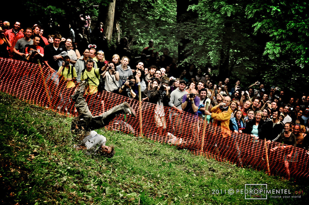 Another determined competitor on an EPIC (out of many) fall/crash after failing to keep up with his legs due to the steepness of the terrain..Gloucestershire Cheese Rolling festival. Cooper's Hill, UK.