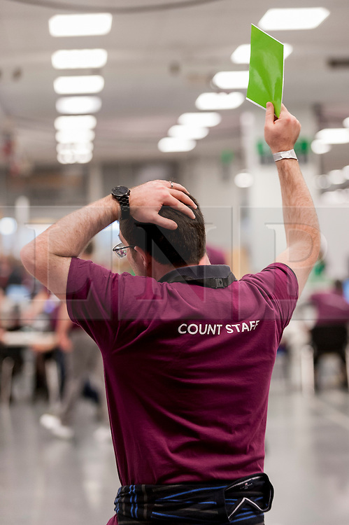 © Licensed to London News Pictures. 06/05/2016. London, UK. A counter signals for a new box of voting papers to be fed into his automated counting machine.  Votes for the London Mayoral elections and London Assembly Members are collated and counted at Olympia in Kensington, one of three official counting houses. Photo credit : Stephen Chung/LNP