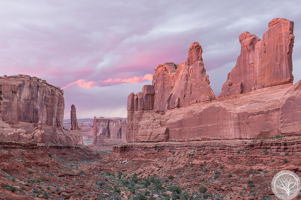 A hint of light prior to sunset adds a burst of color to incoming storm clouds. Park Avenue in Arches National Park, Utah.