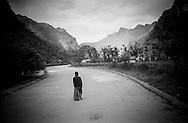 Mysterious silhouette of a lone Vietnamese Hmong man walking on a deserted road, Ha Giang Province, Vietnam, Southeast Asia