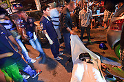 """02 OCTOBER 2009 -- BANGKOK, THAILAND: People pull up a sheet to look at a man who died in a motorcycle accident in Bangkok. The 1,000 plus volunteers of the Poh Teck Tung Foundation are really Bangkok's first responders. Famous because they pick up the dead bodies after murders, traffic accidents, suicides and other unplanned, often violent deaths, they really do much more. Their medics respond to medical emergencies, from minor bumps and scrapes to major trauma. Their technicians respond to building collapses and traffic accidents with heavy equipment and the """"Jaws of Life"""" and their divers respond to accidents in the rivers and khlongs of Bangkok. The organization was founded by Chinese immigrants in Bangkok in 1909. Their efforts include a hospital, college tuition for the poor and tsunami relief.   PHOTO BY JACK KURTZ"""