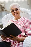 Portrait of senior woman holding book, smiling