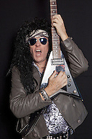 Portrait of senior man wearing sunglasses playing guitar over black background