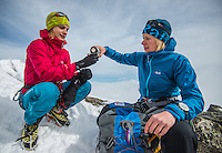 A female mountaineer pours warm tea for her climbing partner on a cloudy Winter afternoon on a snowy rdige of Aiguilles Marbrées in Mont Blanc Massif.