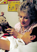 Pediatric nurse with young patient as she listens to his stuffed animals heartbeat.