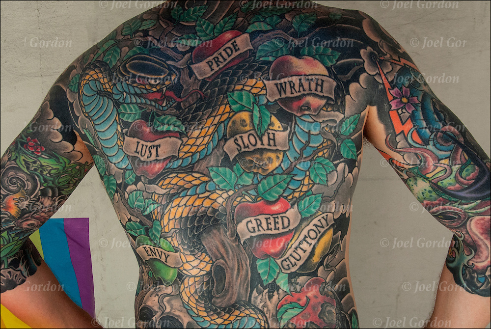 Close up of  tattoos of the seven deadly sins on his whole back side.<br /> <br /> The seven deadly sins, or the capital vices or cardinal sins, is a classification of vices (part of Christian ethics) the sins are wrath, greed, sloth, pride, lust, envy, and gluttony. <br /> <br /> Body art or tattoos has entered the mainstream it is known longer considered a weird kind of subculture.<br /> <br /> Tattoos are no longer just a male thing, young women are just as likely to get a tattoo as males.<br /> <br /> &quot;According to a 2006 Pew survey, 40% of Americans between the ages of 26 and 40 have been tattooed&quot;.