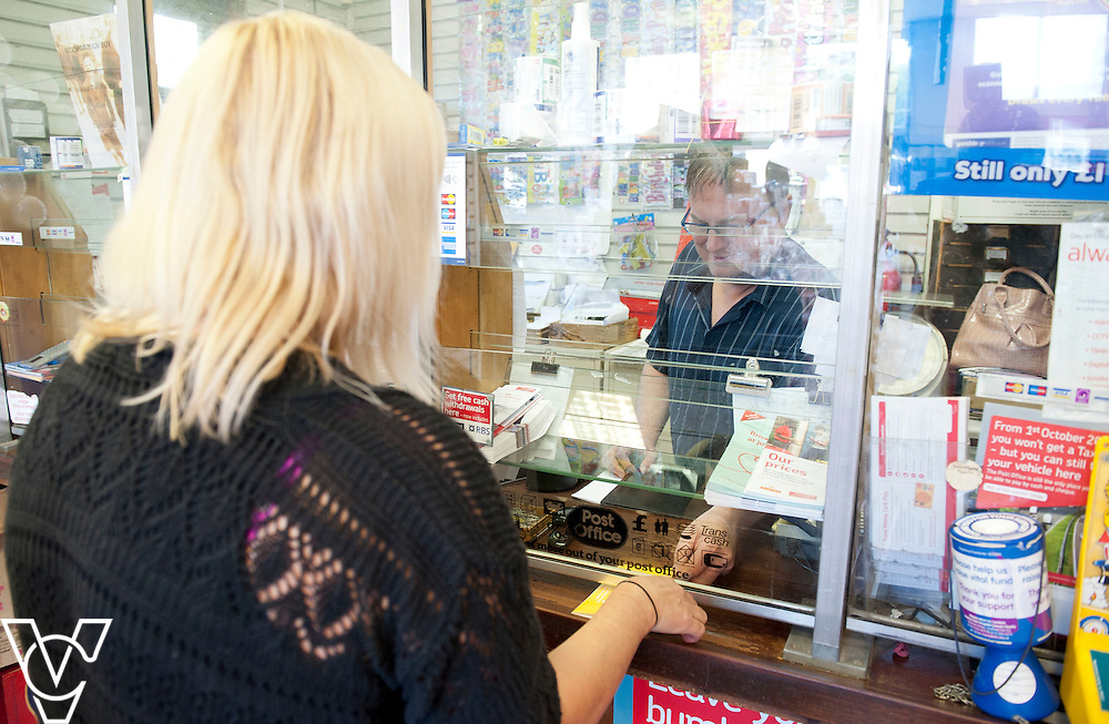 Pictured is Postmaster Dave Lant serving customer Natalie Campbell<br /> <br /> Oughtibridge Post Office, Sheffield.<br /> Date: July 14, 2015