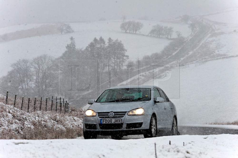 © Licensed to London News Pictures. 29/03/2016. Builth, Powys, Wales, UK. Motorists negotiate the B4520 (Brecon Road) between Builth Wells and Brecon on the high moorland of the Mynydd Epynt range during a sudden snowfall this afternoon. Photo credit: Graham M. Lawrence/LNP