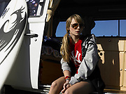 Young woman sitting in the open side door of van with surfboard leaning against door.