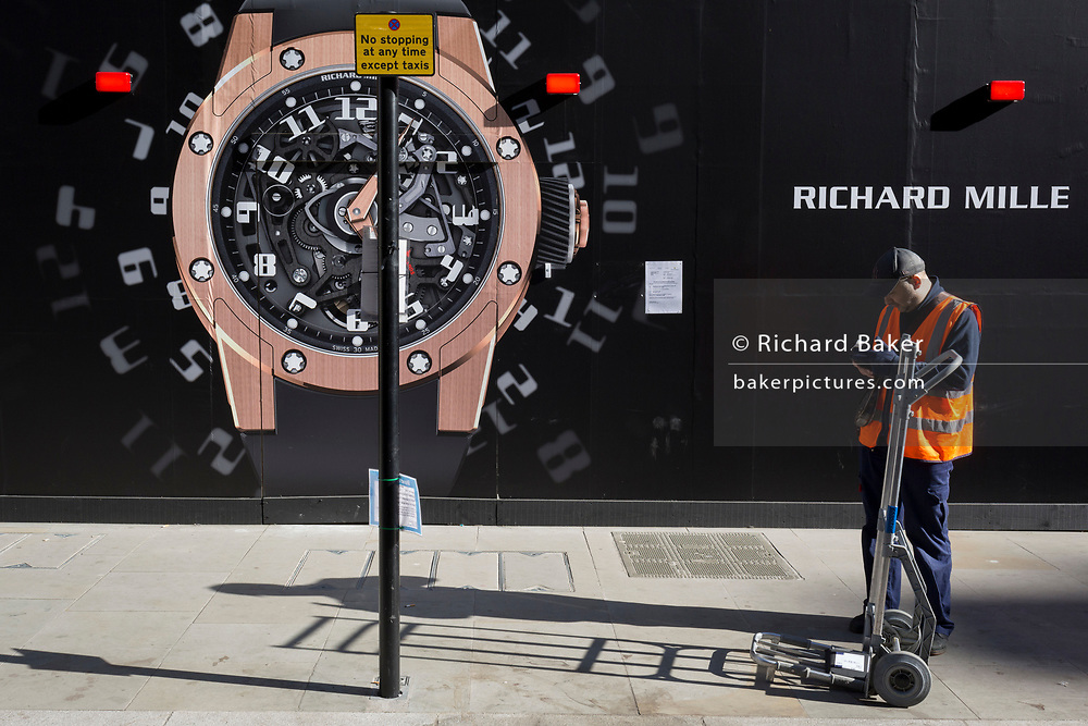 A courier checks his delivery device next to a construction hoarding of a watch outside the new Richard Mille shop in New Bond Street, on 25th February 2019, in London, England.