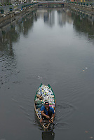 In a city which is sinking a man collects plastic bottles and containers on a canal, Central Jakarta, Indonesia.