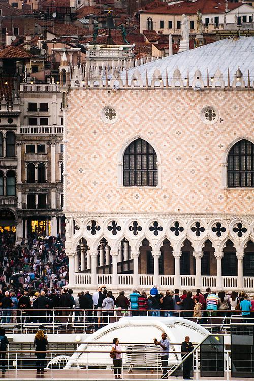 Venezia vista dall'alto: turisti fotografano il Palazzo Ducale dal ponte superiore di una grande nave da crociera.