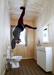 EDITORS NOTE:<br /> THIS IMAGE HAS BEEN ROTATED 180 DEGREES An employee holds onto the toilet seat in the bathroom in 'The Upside Down House', a zero-gravity illusion experience, in The Triangle in Bournemouth, Dorset.