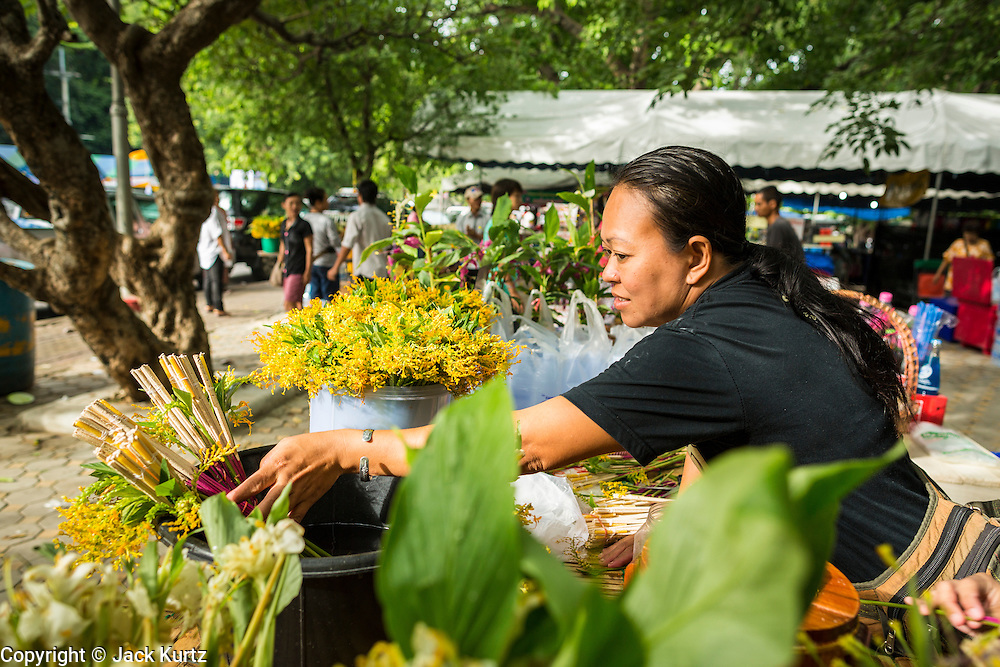 """22 JULY 2013 - PHRA PHUTTHABAT, THAILAND:  Flower vendors set out """"dancing lady ginger"""" flowers for people to buy during the Tak Bat Dok Mai at Wat Phra Phutthabat in Saraburi province of Thailand, Monday, July 22. Wat Phra Phutthabat is famous for the way it marks the beginning of Vassa, the three-month annual retreat observed by Theravada monks and nuns. The temple is highly revered in Thailand because it houses a footstep of the Buddha. On the first day of Vassa (or Buddhist Lent) people come to the temple to """"make merit"""" and present the monks there with dancing lady ginger flowers, which only bloom in the weeks leading up Vassa. They also present monks with candles and wash their feet. During Vassa, monks and nuns remain inside monasteries and temple grounds, devoting their time to intensive meditation and study. Laypeople support the monastic sangha by bringing food, candles and other offerings to temples. Laypeople also often observe Vassa by giving up something, such as smoking or eating meat. For this reason, westerners sometimes call Vassa the """"Buddhist Lent.""""    PHOTO BY JACK KURTZ"""