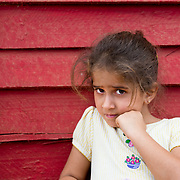 Portrait of shy young Cuban girl in front of red wall