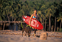 Alicia Ritter walking on beach with Lexi before surfing along the coast of Michoacan, Mexico.<br />