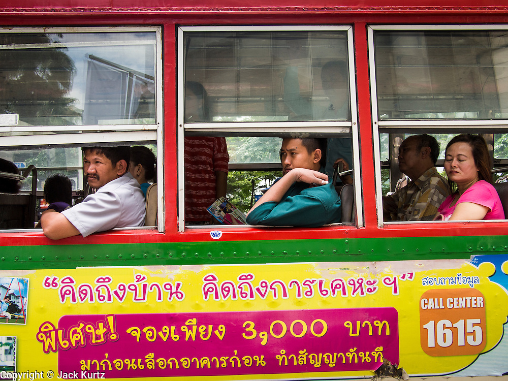 """23 AUGUST 2013 - BANGKOK, THAILAND:    Passengers ride a public bus in Bangkok. Thailand entered a """"technical"""" recession this month after the economy shrank by 0.3% in the second quarter of the year. The 0.3% contraction in gross domestic product between April and June followed a previous fall of 1.7% during the first quarter of 2013. The contraction is being blamed on a drop in demand for exports, a drop in domestic demand and a loss of consumer confidence. At the same time, the value of the Thai Baht against the US Dollar has dropped significantly, from a high of about 28Baht to $1 in April to 32THB to 1USD in August.    PHOTO BY JACK KURTZ"""
