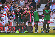 Leeds United defender Stuart Dallas (15) scores a goal and celebrates with team mates to make the score 0-1 during the EFL Sky Bet Championship match between Stoke City and Leeds United at the Bet365 Stadium, Stoke-on-Trent, England on 24 August 2019.