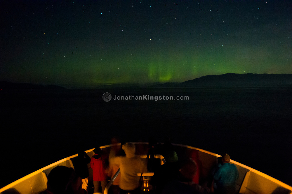 Northern lights or Aurora Borealis light the sky over the bow of a small cruise ship sailing at night in Alaska's inside passage near Glacier Bay National Park.