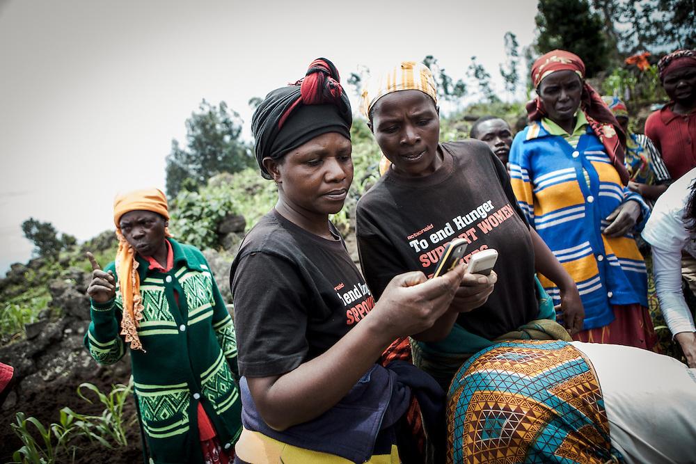 Two women use their mobile phones. Shingiro District, Rwanda