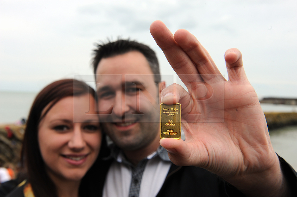 """© Licensed to London News Pictures. 30/08/2014<br /> Kirsty Henderson age 26 and Kevin Wood age 28 from Canterbury are the finders of the first declared gold bar in Folkestone,Kent. <br /> Folkestone Gold Beach.<br /> £10,000 of buried treasure at Outer Harbour beach near Sunny Sands, Folkestone,Kent.<br /> The installation, entitled """"Folkestone Digs"""", is funded by Bristol-based designers Situations and the idea for the project came from Berlin-based artist Michael Sailstorfer.<br /> The small gold bars - similar to a dog tag - come in two sizes, worth around £250 and £500.<br /> <br /> (Byline:Grant Falvey/LNP)"""