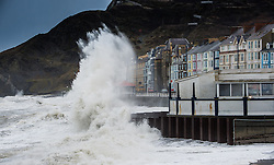 """© Licensed to London News Pictures. 23/02/2015. Aberystwyth, UK The high 'supertide' at 10.30, combined with strong winds bring huge waves crashing into the sea wall and promenade at Aberystwyth on the west wales coast . <br /> Flood warnings are in place for many 'at risk' areas on the Welsh seaboard, including Aberystwyth, with further alerts for much of the rest of the Welsh coastline. Natural Resources Wales warned of """"dangerous conditions"""" that could see tides breach sea and river defences. Photo credit : Keith Morris/LNP"""