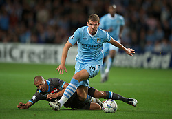 MANCHESTER, ENGLAND - Wednesday, September 14, 2011: Manchester City's Edin Dzeko in action against SSC Napoli's Gokhan Inler during the UEFA Champions League Group A match at the City of Manchester Stadium. (Photo by Chris Brunskill/Propaganda)