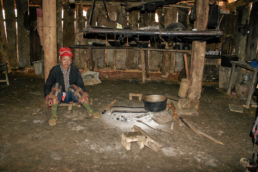 Red H'mong village woman in the kitchen of her wooden home.  Walls of vertical slats abut each other but show many openings where they do not meet.  The kitchen fire is an area on the floor, covered with white ash..  North Vietnam.