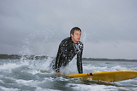 Surfer pulling himself up onto surfboard in water