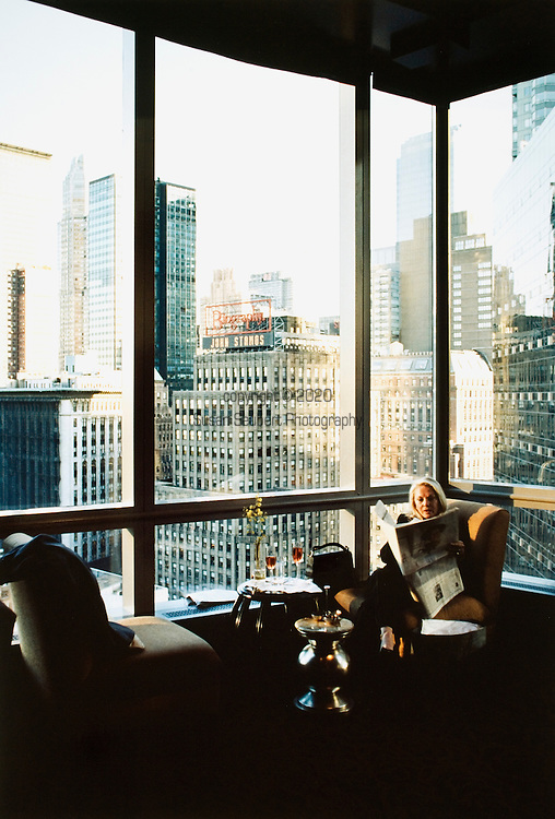 A woman relaxes at happy hour in the Lobby Lounge of the Mandarin Oriental in New York City.  The lounge sits on an upper floor at the Columbus Circle address and has dramatic views of Central Park and New York City's dramatic skyline.
