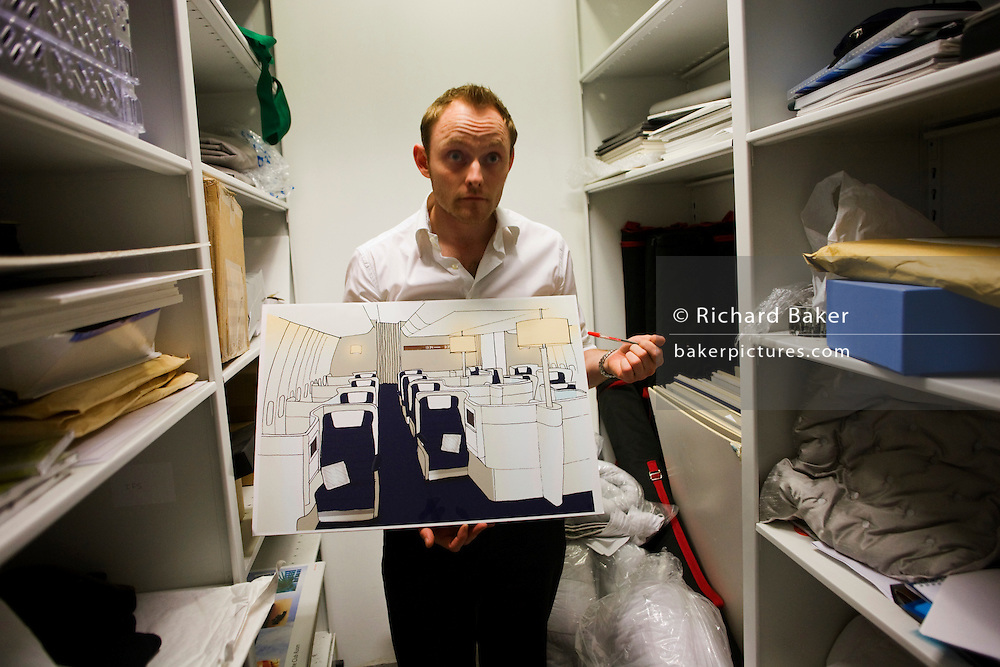 "In an office stock room, an archivist in British Airways' Customer Experiences Divition shows some conceptual design ideas for future Business Class cabin layouts, seen at the airline's corporate headquarters at Waterside at Harmondsworth near Heathrow Airport. Having listened to their passengers' ideas for what they'd like to experience in their long-haul cabins, BA regularly come up with ways to make the flight for premium users a reason to become loyal fare-payers. From writer Alain de Botton's book project ""A Week at the Airport: A Heathrow Diary"" (2009). .."