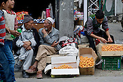 A young man sells apricots, two older gentlemen exchange stories and two boys walk by, the Kargil bazaar.