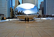 "Visitors admire the Cloud Gate sculpture in Millinnium Park, Chicago Illinois, January 11, 2009.  Cloud Gate is a three-story, 110-ton steel sculpture that has been dubbed by residents as ""The Bean"". The sculpture is the work of world-renowned artist Anish Kapoor and is the first of his public art in the United States. The piece was privately funded and the total cost was $23 million, considerably more than the original estimate of $6 million. Cloud Gate is a highly-polished reflective steel sculpture that is meant to resemble a drop of mercury hovering at the point of landing on a plaza of the park."