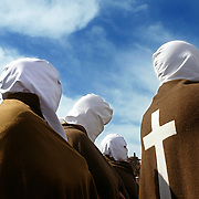 """A person takes a photograph of a group of """"Picados"""", penitents who flagellate themselves as an act of religious penance during the celebration of the Via Crucis procession on Good Friday in San Vicente de la Sonsierra, 14 April 2006. Hundreds of Easter processions take place around the clock in Spain during Holy Week drawing thousands of visitors."""