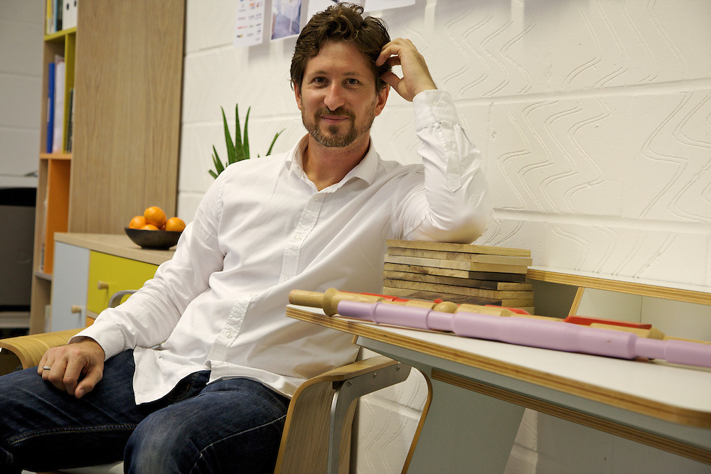 Leonhard Pfeifer, furniture designer, in his Hackney studio, London with the Abbeywood sideboard (left) manufactured in Estonia by Woodman and the Slope desk (right, it was awarded Design Guild Mark 2014) manufactured in Germany by Müller Möbelwerkstätten. Wood and color samples from the studio on the desk.<br /> CREDIT: Vanessa Berberian for The Wall Street Journal<br /> GURU-Pfeifer