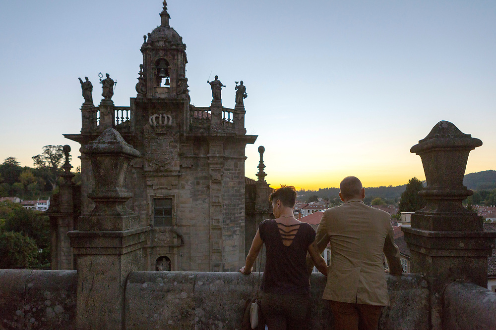 SANTIAGO DE COMPOSTELA, SPAIN - 9th of October - Two tourists admiring Church architecture at sunset in Santiago de Compostela, Galicia, Spain.