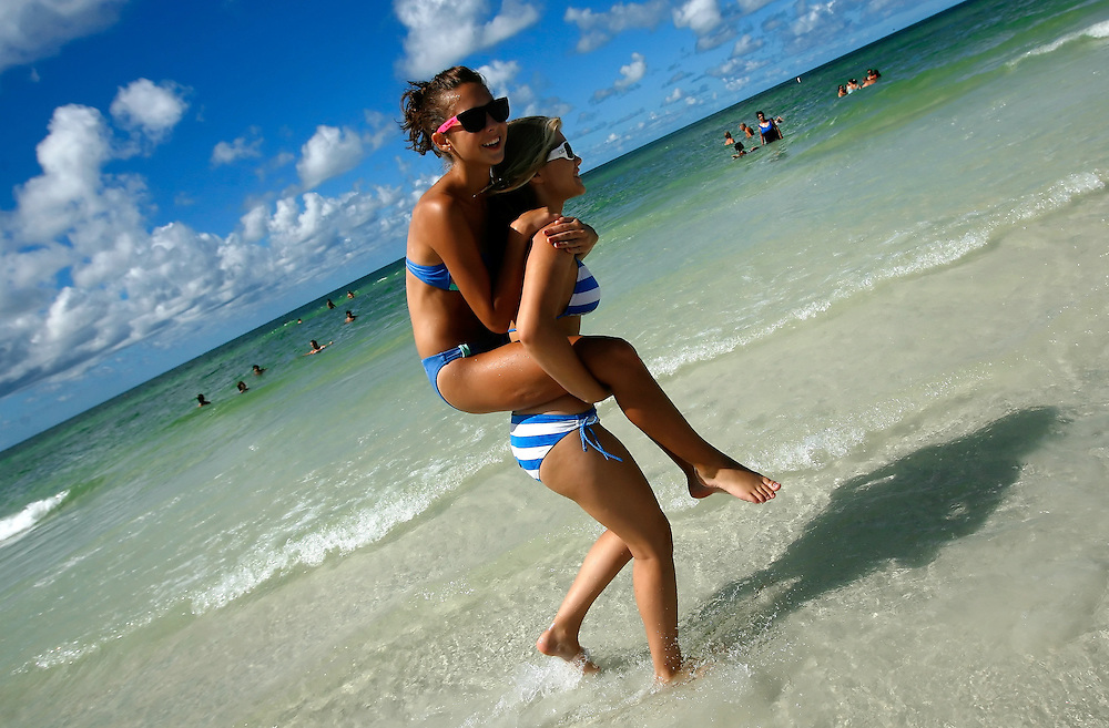 SIESTA KEY, FL -- August 22, 2009 -- Meagan Vanderbeck, 14, gives Casey Chapman, 14, both of Port Charlotte, Fla., a piggy-back ride as they hagn with friends at Siesta Key Public Beach on Siesta Key in Sarasota, Fla., on Saturday August 22, 2009.  Siesta Key Beach is known for its soft white sand, which stays cool even in the dead heat of summer.  Summer is becoming a more popular time to visit Siesta Key out of season with shorter lines, cheaper rates, and more room to plop a towel and umbrella down in said sand.