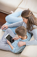 High angle view of mother and son using tablet PC on sofa