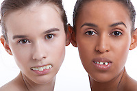 Portrait of two young women with fake teeth against white background