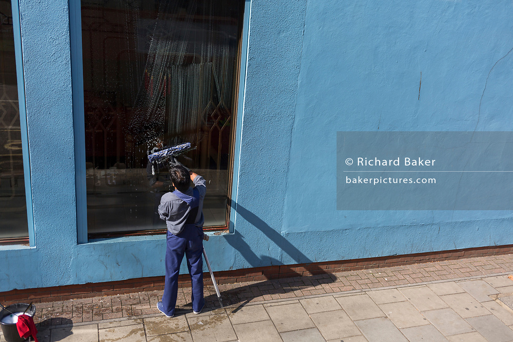 A window cleaner soaps a tall window near a blue wall on the Walworth Road, near Elephant And Castle, on 12th September 2017, in London, England.